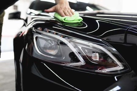 A man cleaning car with microfiber cloth, car detailing (or valeting) concept.