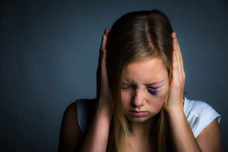 Young blonde girl with hands over ears, scared and intimidated
