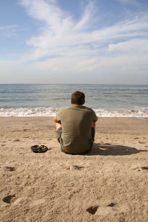 solitary man sitting on beach watching the waves
