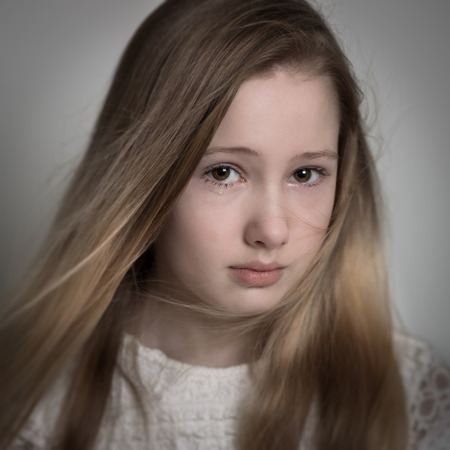 Young blond teenage girl with long hair with a sad face, crying isolated against a grey background