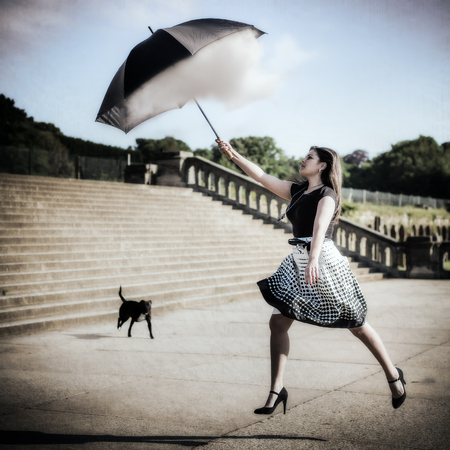 Artistic grunge style composite photo of a woman with black top, dotted skirt and long hair jumping up and catching a dream cloud with her umbrella in front of concrete stairs and a dog in the background.