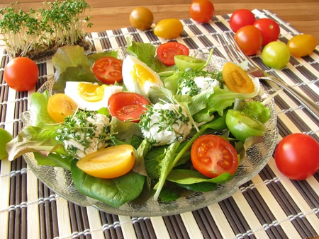 Salad with colorful tomatoes and cream cheese balls with cress
