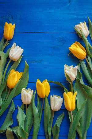 Photo pour Row of tulips on blue wooden background with space for message. Women's or Mother's Day background. Top view - image libre de droit