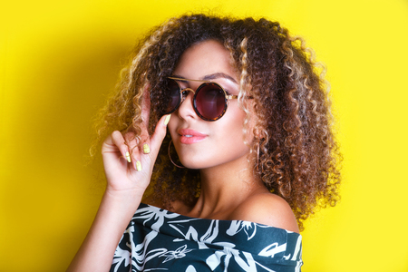 Photo pour portrait indoors of a young afro american woman in sunglasses. Yellow background. Lifestyle. - image libre de droit