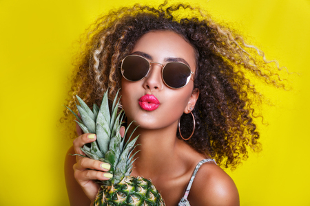 Photo pour Fashion summer portrait afro american girl in sunglasses and pineapple over yellow background - image libre de droit