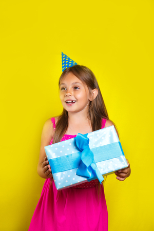 Studio portrait of a little girl wearing a party hat on her birthday. Cute girl open her birthday gift box