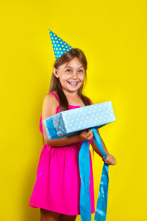 Unwrapping gift . Studio portrait of a little girl wearing a party hat on her birthday. Cute girl open her birthday gift box