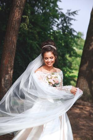 Foto de Beautiful bride in fashion wedding dress on natural background. Wedding day. - Imagen libre de derechos