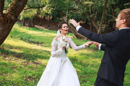 Foto de Happy handsome groom and beautiful bride in white dress laughing and dancing in the park - Imagen libre de derechos