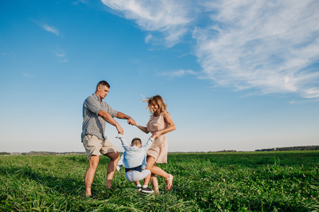 Photo pour Mother and father swinging son in sunnny summer day on meadow - image libre de droit