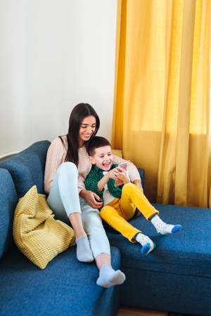Photo pour Beautiful young mom and her little son using a smartphone and smiling while sitting on sofa at home - image libre de droit