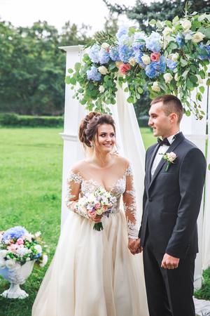 Photo pour Amazing wedding couple near wedding arch . Groom and bride in love - image libre de droit