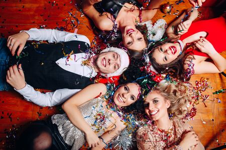 Photo pour Group of friends at club having fun and lying on the floor .New years party - image libre de droit