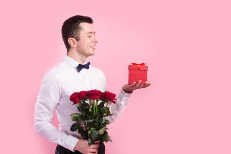 Photo pour Young handsome man with beautiful flower bouquet and red gift box on pink background - image libre de droit
