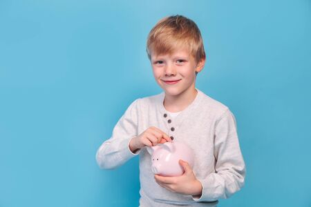 Photo pour Little boy saving money in a piggybank on blue background - image libre de droit