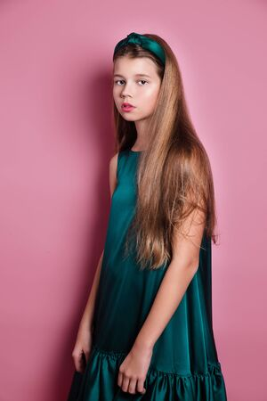 Photo pour Fashion portrait of beautiful young woman in a satin emerald dress on pink studio background - image libre de droit