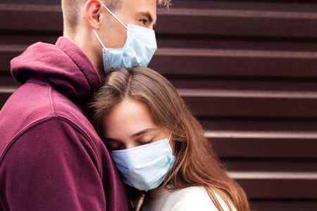 Foto de Young couple hugging wearing a face protection mask in the city since new coronavirus Covid 19 - Imagen libre de derechos