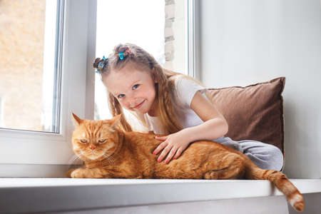 Photo pour Cute child embraces with tenderness and love a red cat on window - image libre de droit
