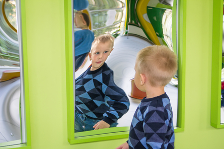 Odessa, Ukraine - OCT 24: Boy playing in carnival distortion mirror in green room
