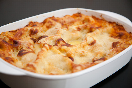 A lasagna in a white baking dish on a black table. An Italian minced vegetable casserole with pasta sheets, baked in a tomato sauce with cheese.