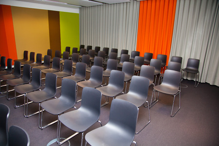 empty seats at an presentation or event in a room with colorful walls.