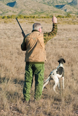Quail hunter in camouflage clothing walking across the field