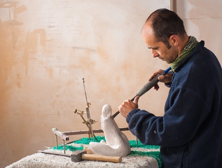 Sculptor working on his art at his workshop