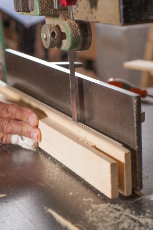 Workplace risks: carpenter working on a sawing table with a bandaged finger