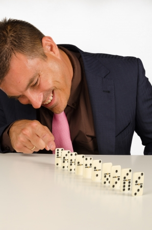 Guy having fun with a row of domino stones