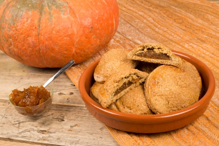 A bowl with homemade pumpkin biscuits next to their main ingredient