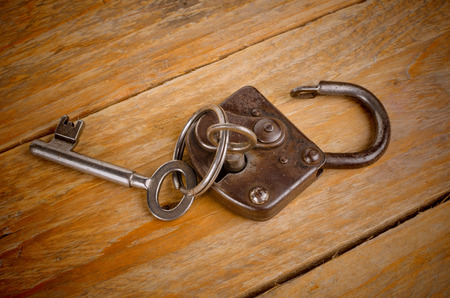 Vintage key inserted in an old padlock
