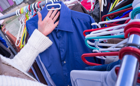 Female hands choosing clothes on a market stall