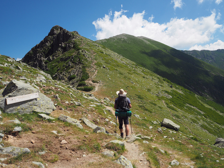 hiker man in hat with heavy backpack walking on GR 20 famous trail in corsician alpes, scenery of high mountain green meadow with blue sky background