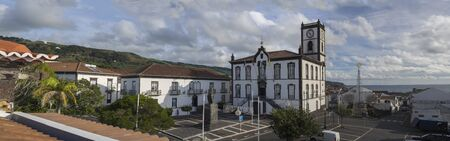 Portugal, VILA FRANCA DO CAMPO, Sao Miguel, Azores, December 28, 2018: Panoramic view on main square in the center of Vila Franca do Campo town with Town Hall with clock tower in colonial style and christmas decoration with sea and green hills, morning bl