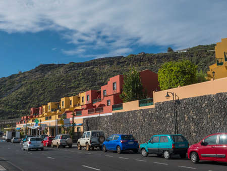 Los Cancajos, La Palma, Canary Islands, Spain, December 22, 2019: Colorful yellow and red apartement houses and parked car at Main road street with view on green mountains and hills