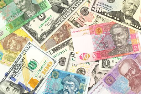 Photo pour some ukrainian hryvnia banknotes and american dollar banknotes mixed indicating bilateral economic relations - image libre de droit