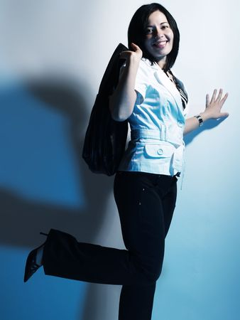 A high-key portrait about a cute stylish woman with black hair who is lighted with blue, she is lifting up her leg and she has an attractive look. She is wearing black pants, a white coat and a stylish handbag.の写真素材