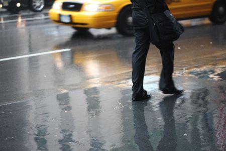 man walking in the rain on a city sidewalk