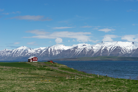 Little red house on the water edge just outside Dalvik, Iceland