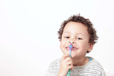 Photo pour little boy brushing his teeth with an electric tooth brush stock image with white background stock photo - image libre de droit