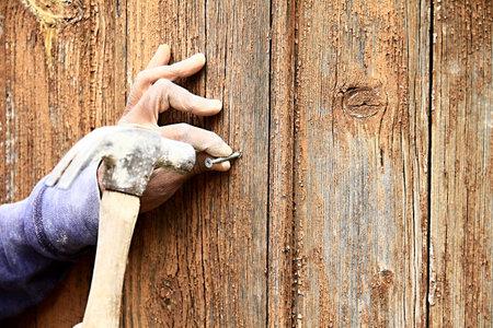Photo pour Carpenter hammering a nail in a wooden door stock photo - image libre de droit