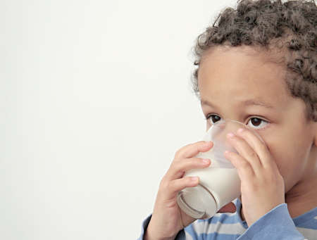 Photo for boy drinking milk for breakfast on white background stock photo - Royalty Free Image