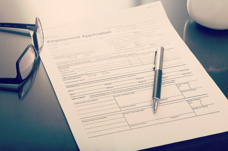 Photo pour Close up of a job application form on desk with pen and glasses - image libre de droit