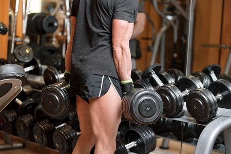 Photo for Closeup shot of unidentifiable muscular male picking up heavy dumbbell weights from equipment rack in modern gym. - Royalty Free Image