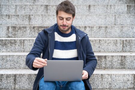Photo for Handsome hipster modern businessman, using laptop in the city, with positive expression. - Royalty Free Image