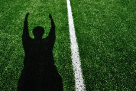 Shadow of American Football Referee Signaling a Touchdown
