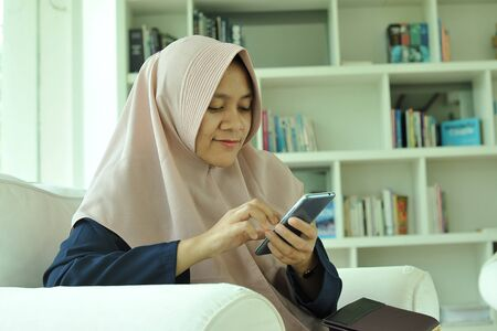 Photo for Portrait of cheerful smiling muslim woman girl using smartphone at living room. - Royalty Free Image