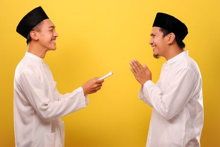 Photo pour Young Asian Muslim man give alms to other muslim on Ramadan Kareem. It's the best time to give alms to everyone need, isolated on yellow background - image libre de droit