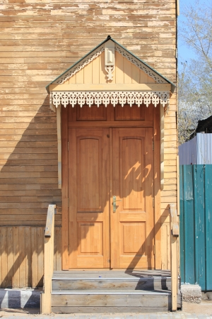entrance in a wooden house with a porch and canopy