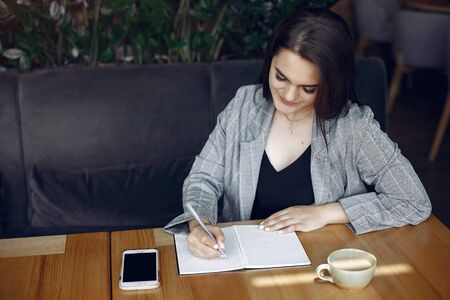 Photo pour Businesswoman sitting at the table in a cafe and working - image libre de droit